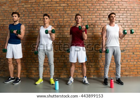 Skillful male athletes lifting weights - stock photo