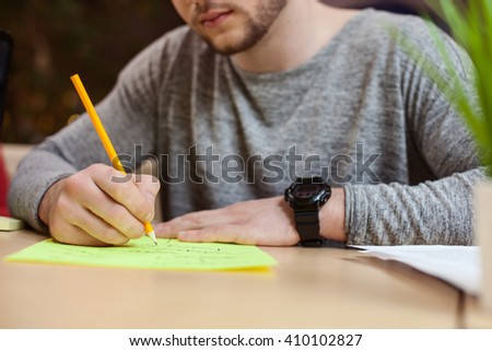 Skillful male student is noting some information - stock photo