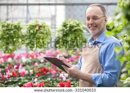 Skillful old florist is standing in garden center. He is holding a folder of documents and writing some notes. The man is looking at camera and smiling - stock photo