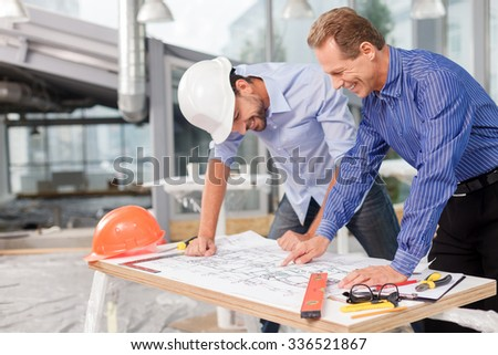 Skillful two engineers are projecting the construction. They are standing near the table with a blueprint on it. The men are looking at sketches and smiling - stock photo