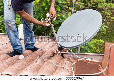 Skillful worker installing satellite dish and television antenna on roof top - stock photo