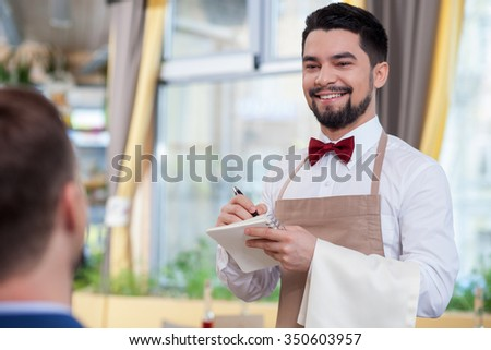 Skillful young waiter is serving a customer and smiling. He is standing and noting an order. The man is looking at the businessman with joy - stock photo