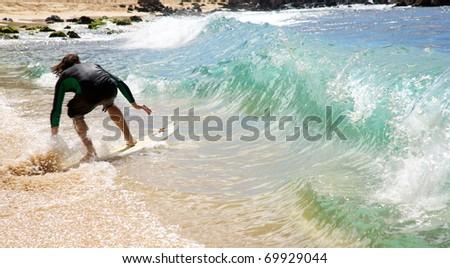 Skimboarding waves at Big Beach in Maui - stock photo