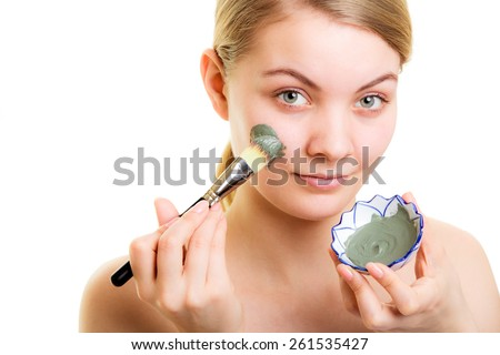 Skin care. Woman applying with brush clay mud mask on face isolated. Girl taking care of dry complexion. Beauty treatment. - stock photo