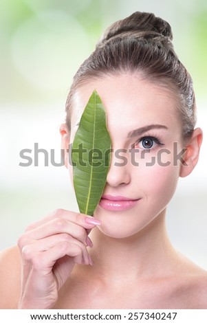 Skin care woman face with green leaf, concept for skin care or organic cosmetics, caucasian - stock photo