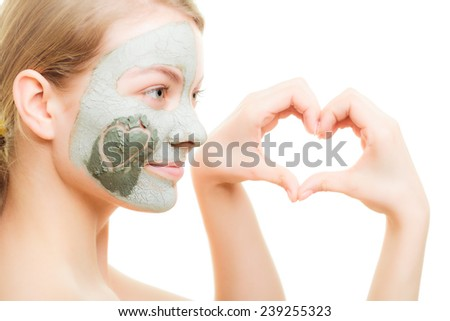 Skin care. Woman in clay mud mask on face with heart on cheek isolated on white. Girl showing symbol of love with hands. Beauty treatment. - stock photo