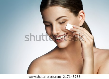 Skin care woman removing face makeup - skin care concept / photocomposition of brunette smiling girl on studio background  - stock photo