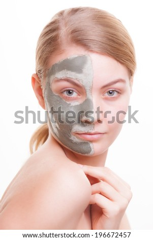 Skin care. Young woman applying clay mask on her face. Girl taking care of her dry compexion. Isolated. Spa and beauty treatment. - stock photo