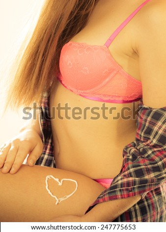 Skincare. Closeup of female body with heart shaped cream. Young woman girl taking care of her dry legs skin applying moisturizer lotion. Beauty treatment. - stock photo