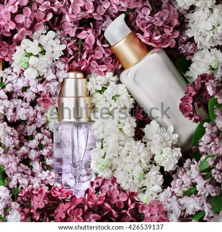 Skincare products - cream and serum - set with fresh lilac, closeup shot, lilac as background. Skincare and beauty concept. - stock photo