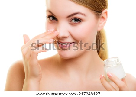 Skincare. Young woman holding lotion jar. Blond girl taking care of her dry complexion applying moisturizing cream isolated. Beauty treatment. - stock photo