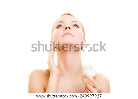 Skincare. Young woman taking care of her dry complexion. Girl applying moisturizing cream isolated. Beauty treatment. - stock photo
