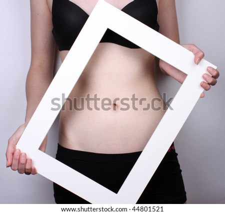 Skinny girl with bellybutton in white frame - stock photo
