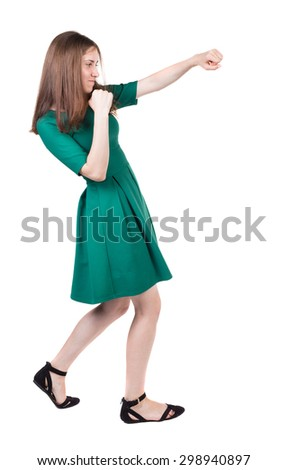 skinny woman funny fights waving his arms and legs. Isolated over white background. A girl in a long green dress boxing. - stock photo