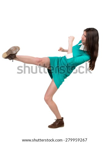 skinny woman funny fights waving his arms and legs. Isolated over white background. The girl in a green dress simply raised her left foot. - stock photo