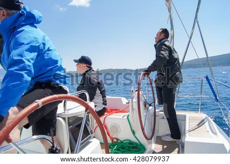 "Skipper managing yacht. Tivat, Montenegro - 26 April, 2016 Regatta ""Russian stream"" in God-Katorskaya bay of the Adriatic Sea off the coast of Montenegro. - stock photo"