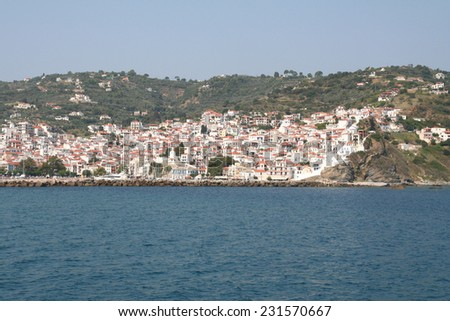 Skopelos Town on Skopelos Island, Greece. The old wall can be seen on the right of the town as the buildings rise up the slope of the hill. A breakwater protects the harbour. - stock photo