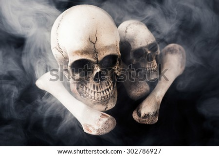 skull and bones with smoke on black background - stock photo