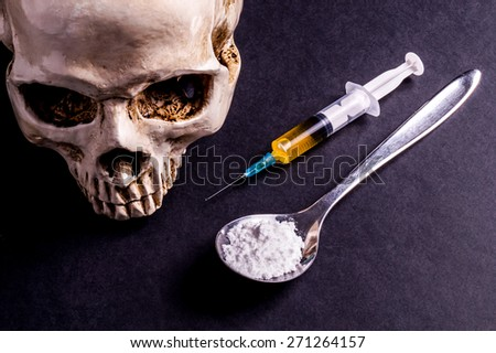 Skull and spray with yellowish liquid. Next to them are a spoon with white powder, which is similar to heroin . Isolated on black - stock photo