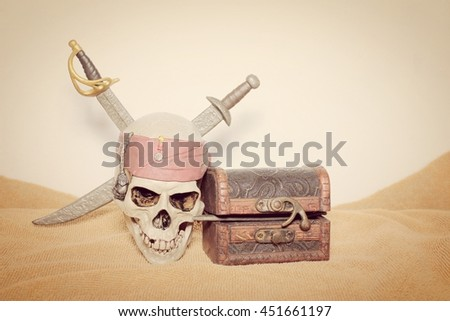 skull and swords pirate of the Caribbean with Old wooden chest on the brown fabric. - stock photo