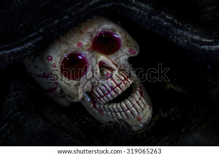 skull in the cloth wrap and blood  over black - stock photo