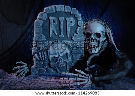Skull monster and tombstone halloween decoration - stock photo