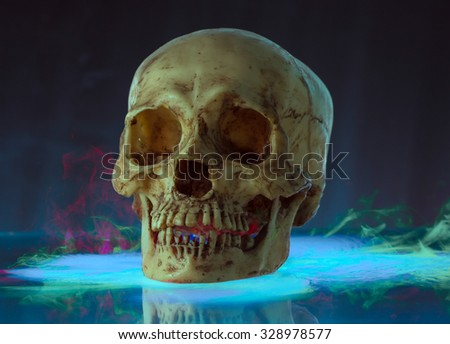 Skull on glass with multi color smoke of ice - stock photo
