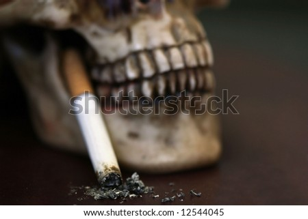 Skull with Burnt Cigarette - stock photo