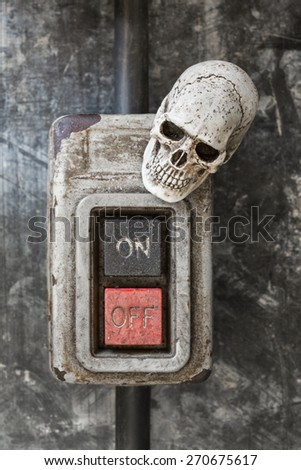 skull with old electric switch on grunge wall, focused at skull - stock photo