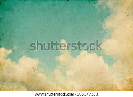 Sky and billowing clouds on a textured vintage paper background with grunge stains and retro colors. - stock photo