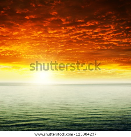 sky and red dramatic sunset over sea - stock photo