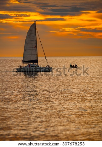 Sky blazing with the last orange light of sunset over a catamaran sailboat, with its sail unfurled, on a tropical sea. - stock photo