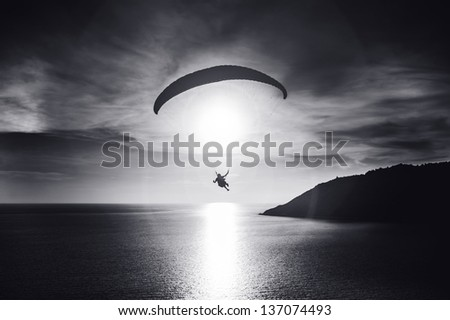Sky diver flies at sunset over the bay. Black and white photo - stock photo