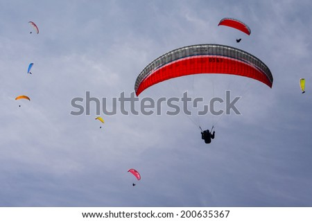 Sky full of paragliders - stock photo