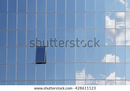 Sky reflected in windows of modern office building - stock photo