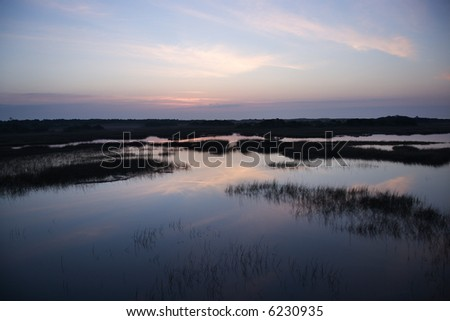 Sky reflecting in water in marsh area on Bald Head Island, North Carolina. - stock photo