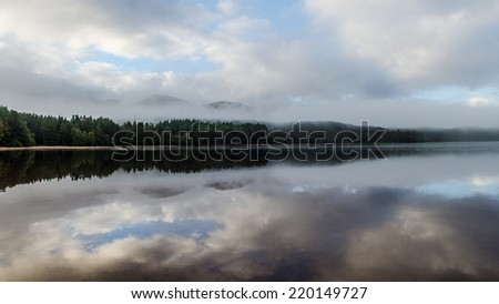 Sky reflections of Loch Morlich - stock photo