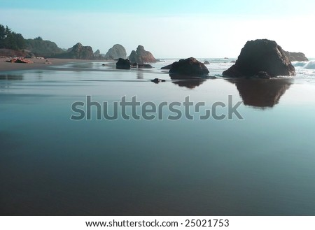 Sky reflects a turquoise hue on the sand of a rocky beach in Oregon - stock photo