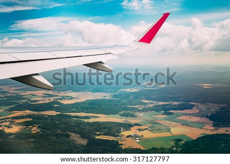 Sky view from airplane window. The window seen forests and colorful fields of Norway in autumn season. - stock photo