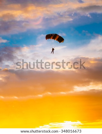 Skydiver On Colorful Parachute In Sunny Sunset Sunrise Sky. Active Lifestyle - stock photo
