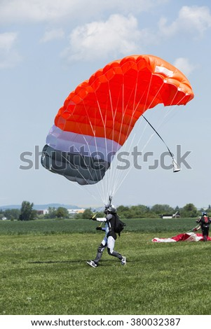 Skydiver with orange parachute runs after landing in a field. - stock photo