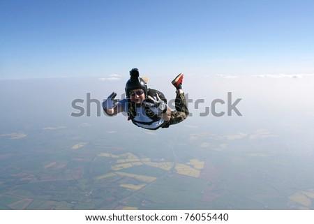 Skydivers waves at the cameraman - stock photo