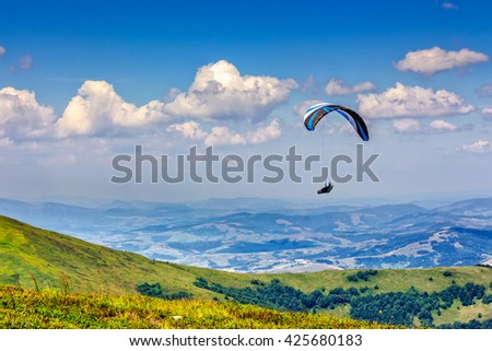 Skydiving  flying over the mountains. parachute extreme sport - stock photo