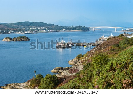 Skye from Kyle of Lochalsh, in the mainland Highlands of Scotland, in a sunny, bright day. Despite the boats and ferries docked at the loch harbor, the main link for transportation is the long bridge. - stock photo