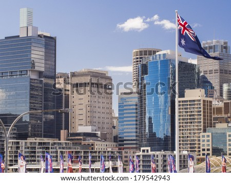 Skyline image showing several Sydney buildings in the Darling Harbour area with a large Australian flag in the foreground. - stock photo