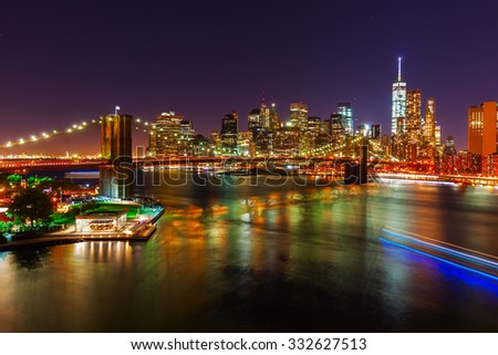 skyline of downtown Manhattan with Brooklyn Bridge and East River in New York City at night - stock photo