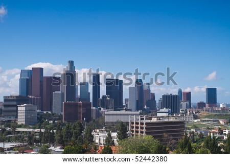 Skyline of Los Angeles shown at early dusk with blue sky. - stock photo