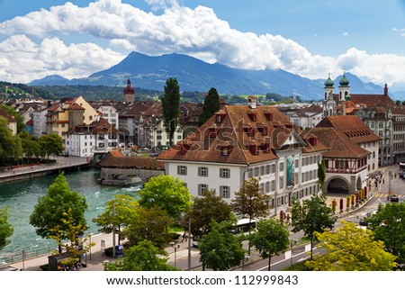 Skyline of Luzern looking over the river towards the old city with the footbridges - stock photo
