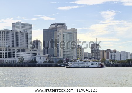Skyline of New Orleans,  Louisiana. Paddlewheel steamboat in foreground. - stock photo