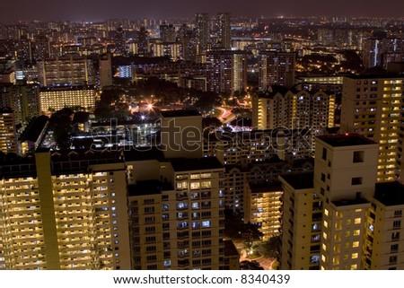 Skyline of Singapore suburbs at night showing blocks of public housing apartments - stock photo